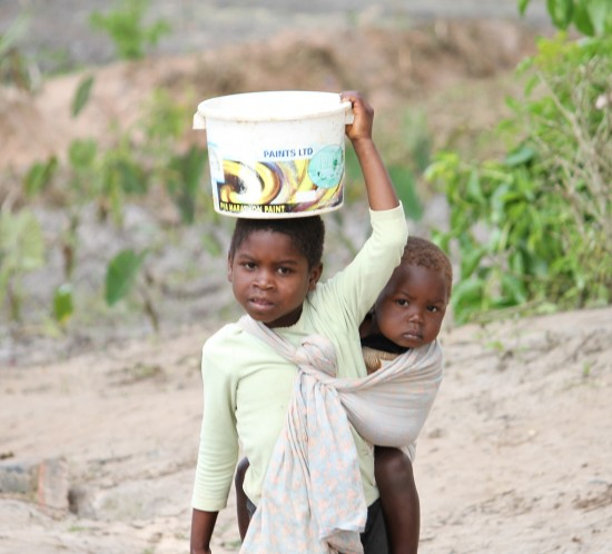 young girl carrying water