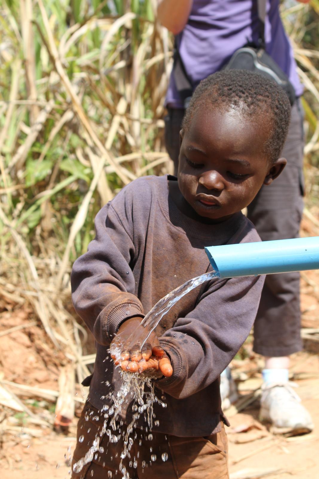 boy washes hands at pump