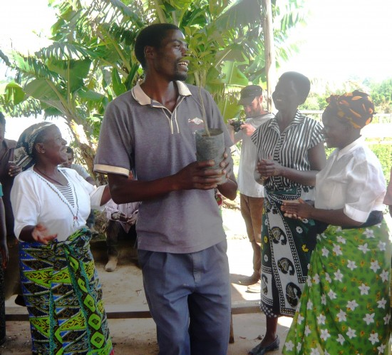 Benidicto demonstates plant care to farm visitors