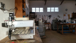 CNC machine in workshop with lathe behind