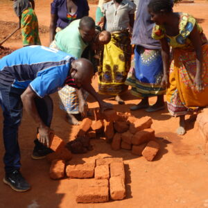 2. village women building large stove with Peter
