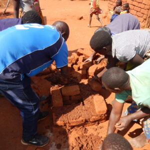 4. village women building large stove with Peter