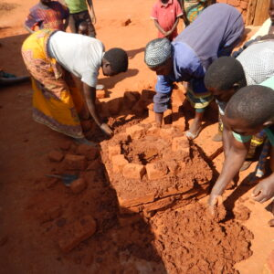 6. village women building large stove with Peter