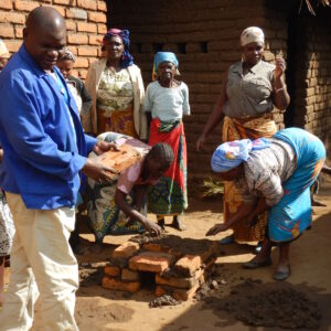 Peter building large stove with village women